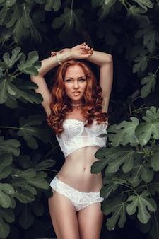 Retrato de moda de joven hermosa mujer sexy con el pelo rojo ondulado largo. chica guapa en sujetador blanco o lencería en el jardín de verano. retrato de colores de tonos de estilo de moda.