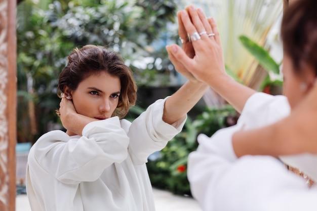 Retrato de moda de joven mujer caucásica modelo profesional en blazer blanco y cadena de plata mirar en espejo en villa de lujo