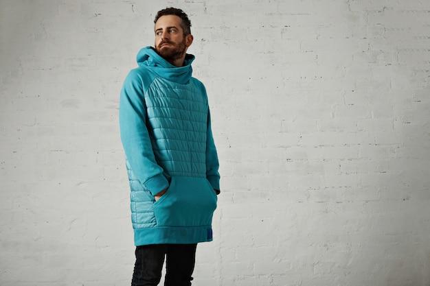 Retrato de moda de un joven pensativo en una sudadera con capucha larga cálida acolchada azul claro en la pared blanca