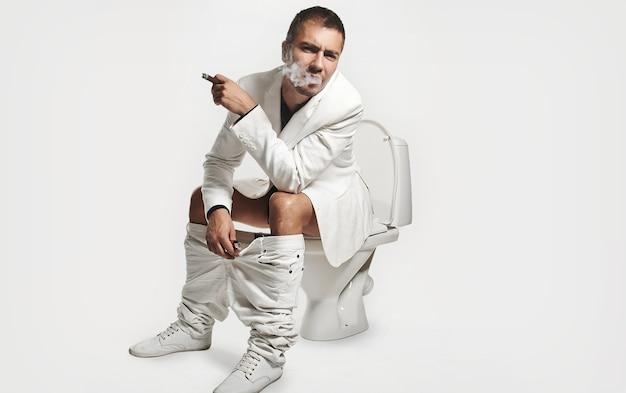 Retrato de moda joven sentado en el inodoro