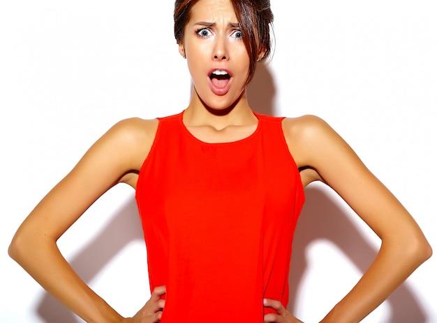 Retrato de moda linda mujer joven modelo en un vestido rojo sobre una pared blanca