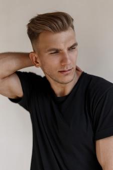 Retrato de moda de un modelo de hombre americano joven guapo con un peinado en una camiseta negra en una pared de luz
