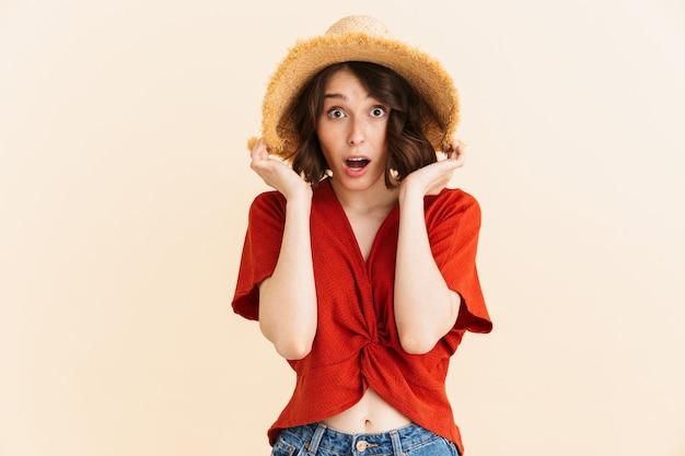 Retrato de moda morena vacaciones mujer vistiendo sombrero de paja expresando sorpresa aislado