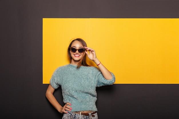 Retrato de moda de una mujer atractiva y elegante con gafas de sol