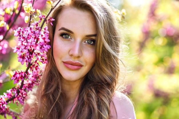 Retrato de moda de mujer bonita elegante tierna con grandes sí verdes y labios carnosos, maquillaje fresco natural y pelos largos y esponjosos de cerca, pintura ordenada árbol floreciente de sakura, tiempo soleado de primavera.