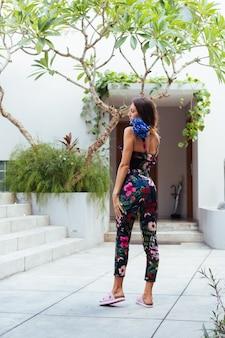 Retrato de moda de mujer caucásica en elegante mono de verano con flores fuera de villa