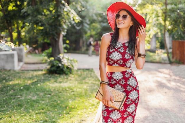 Retrato de moda de mujer elegante atractiva sonriente caminando en el parque en traje de verano vestido estampado, con accesorios de moda, bolso, gafas de sol, sombrero rojo, relajarse en vacaciones