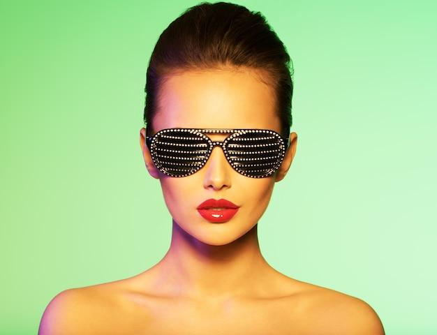 Retrato de moda de mujer con gafas de sol negras con diamantes. colores saturados