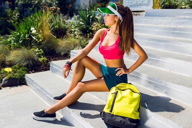 Retrato de moda de mujer hermosa joven en elegante uniforme deportivo con mochila de neón y visera transparente va a jugar al tenis en un cálido y soleado día de verano.