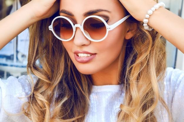Retrato de moda de mujer hermosa con piel perfecta y gran sonrisa increíble de cerca, tiene pelos rizados esponjosos rubios, vistiendo un suéter de destellos blancos, pulsera de perlas y gafas de sol redondas.