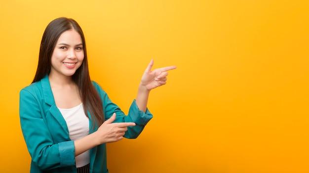Retrato de moda de mujer hermosa en traje verde mostrando algo en la mano en la pared amarilla