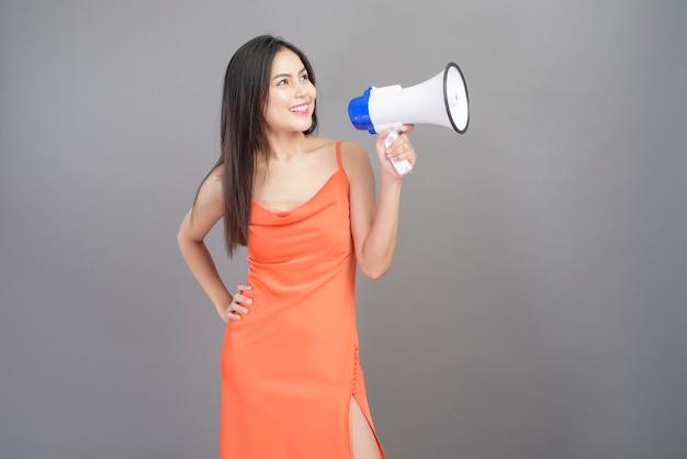 Un retrato de moda de mujer hermosa con un vestido naranja está usando megáfono aislado sobre fondo gris studio