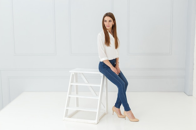 Retrato de moda de mujer en jeans en estudio de luz