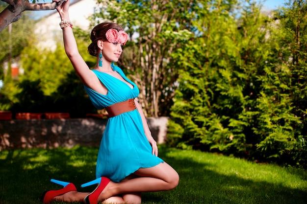 Retrato de moda de mujer joven y bella modelo dama mujer con peinado en vestido azul brillante posando al aire libre sentado en la hierba verde cerca de bush con flores en el cabello