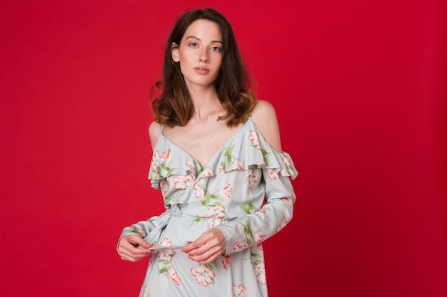 Retrato de moda de mujer joven y bonita en vestido estampado azul en estudio rojo