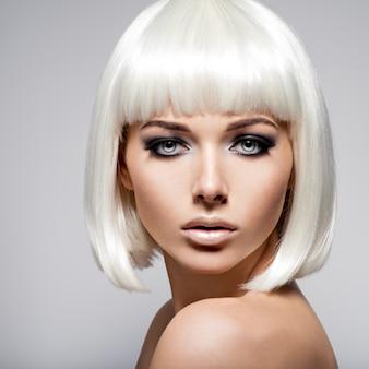 Retrato de moda de mujer joven con cabellos rubios y maquillaje negro de ojos