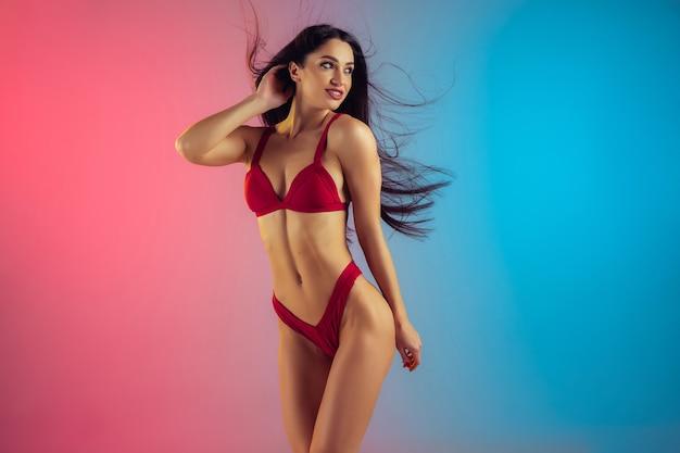 Retrato de moda de mujer joven y deportiva en elegante traje de baño rojo de lujo en pared degradada cuerpo perfecto listo para el verano