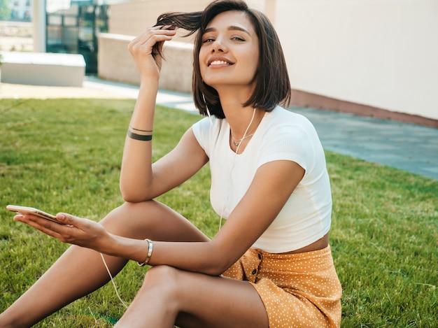 Retrato de moda de mujer joven con estilo hipster. chica con lindo traje de moda. modelo sonriente disfrutar de sus fines de semana, sentada en el parque. mujer escuchando música a través de auriculares