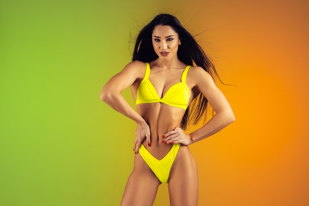 Retrato de moda de mujer joven en forma y deportiva en elegante traje de baño de lujo amarillo. cuerpo perfecto listo para el verano.