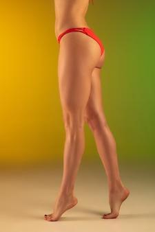 Retrato de moda de mujer joven en forma y deportiva en elegante traje de baño de lujo rosa en gradiente. cuerpo perfecto listo para el verano.