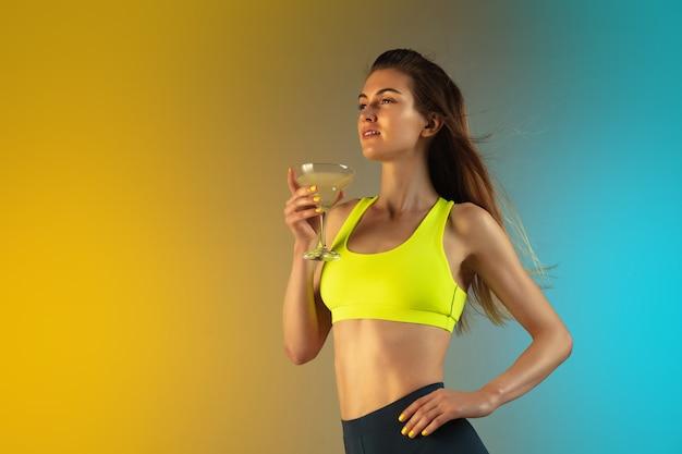 Retrato de moda de mujer joven en forma y deportiva sobre fondo degradado. cuerpo perfecto listo para el verano.
