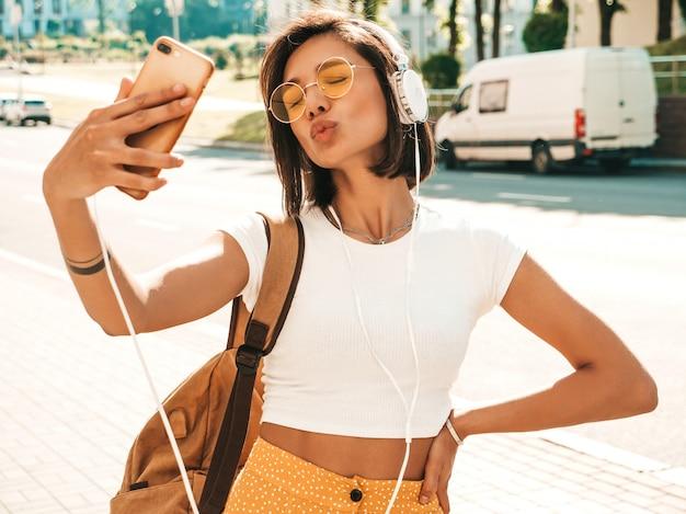 Retrato de moda de mujer joven inconformista elegante caminando en la calle. chica haciendo selfie. modelo sonriente disfrutar de sus fines de semana con mochila. mujer escuchando música a través de auriculares