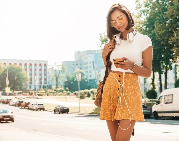 Retrato de moda de mujer joven inconformista elegante caminando en la calle. chica con lindo traje de moda. modelo sonriente disfrutar de sus fines de semana, viajar con mochila. mujer escuchando música a través de auriculares