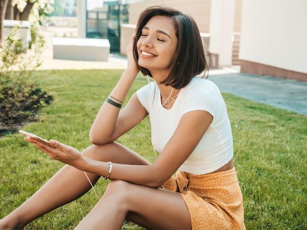 Retrato de moda de mujer joven inconformista elegante sentado en el césped en el parque. chica teje atuendo de moda. modelo sonriente disfrutar de sus fines de semana. mujer escuchando música a través de auriculares. vista superior