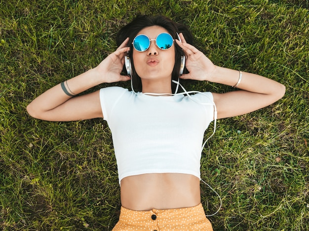 Retrato de moda de mujer joven inconformista elegante tirado en el pasto en el parque. chica teje atuendo de moda. modelo sonriente disfrutar de sus fines de semana. mujer escuchando música a través de auriculares. vista superior