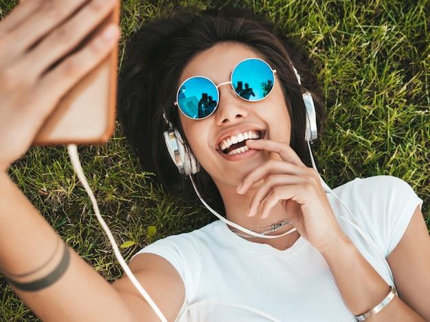 Retrato de moda de mujer joven inconformista elegante tirado en el pasto en el parque. chica teje traje de moda. modelo sonriente haciendo selfie. mujer escuchando música a través de auriculares. vista superior