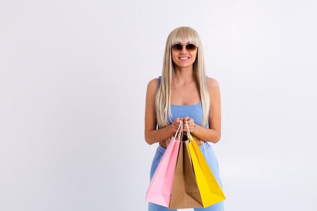 Retrato de moda de mujer joven rubia con cabello lacio largo hermoso con bolsas de colores en el estudio sobre un fondo blanco.