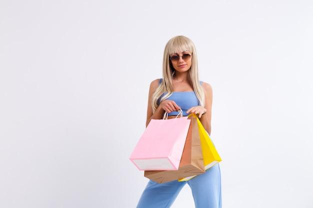 Retrato de moda de mujer joven rubia con cabello lacio largo hermoso con coloridas bolsas de la compra.