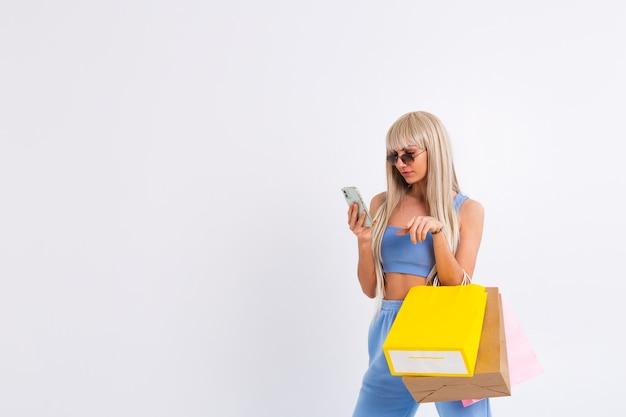 Retrato de moda de mujer joven rubia con cabello largo y liso hermoso mantenga coloridas bolsas de compras