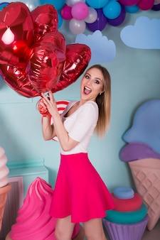 Retrato de moda de mujer joven en vestido rosa con globos de aire, dulces en un colorido
