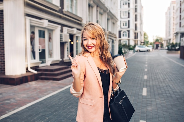 Retrato de moda mujer rubia con pelo largo caminando en chaqueta coral en la calle. ella sostiene una taza de café
