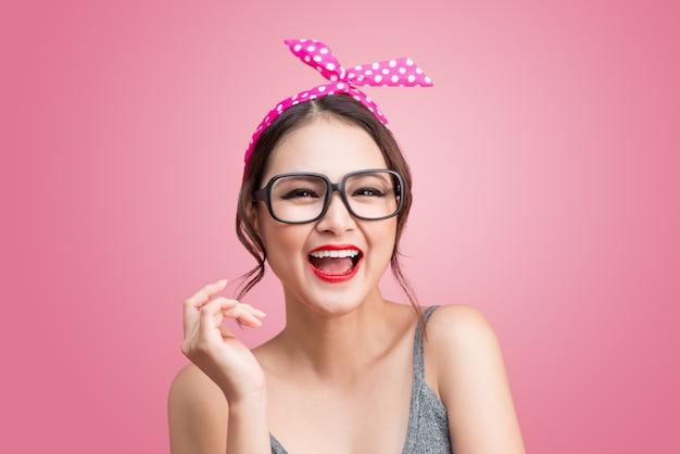 Retrato de moda de niña asiática con gafas de sol sobre fondo rosa.