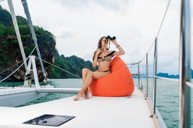 Retrato de moda una niña positiva y hermosa sentada almohada naranja. morena atractiva sonriendo y posando con binoculares en las manos. modelo vistiendo bikini de moda mientras navega