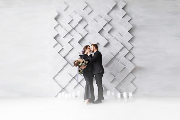 Retrato de moda de novios, novia y novio, sobre cuadrados volumétricos grises