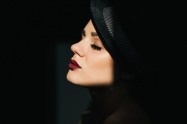 Retrato de moda en el perfil de una joven sexy en un sombrero negro con lápiz labial rojo