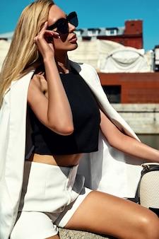 Retrato de moda sexy modelo empresaria moderna en traje blanco con bolso posando en el fondo de la calle detrás del cielo azul