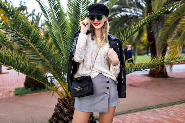 Retrato de moda de vacaciones al aire libre de mujer de belleza posando en la calle de barcelona española con palmeras, estilo callejero de primavera