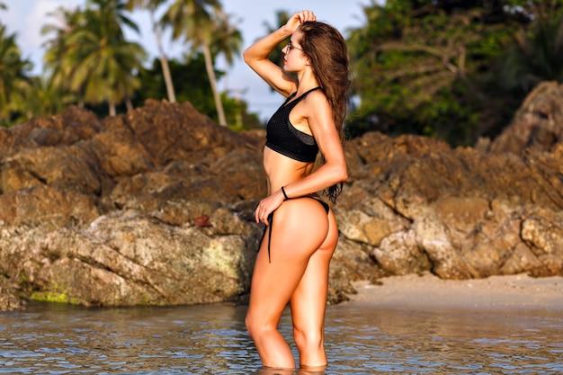 Retrato de moda de verano de mujer bonita posando en la playa, look de moda mojado, cuerpo en forma, bikini negro, cuerpo de fitness delgado