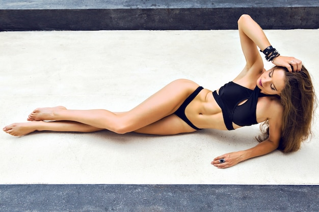 Retrato de moda de verano de mujer impresionante con cuerpo bronceado delgado deportivo