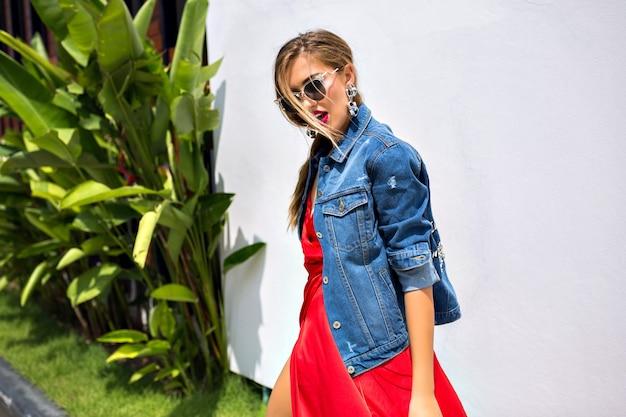 Retrato de moda de verano o impresionante chica de moda elegante posando afuera en un país tropical, con un elegante vestido de lujo y una chaqueta de mezclilla de moda, bailando y divirtiéndose.