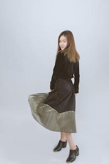 Retrato del modelo asiático que lleva el vestido largo que sonríe en gris. vista posterior femenina asiática mira a cámara en estudio.