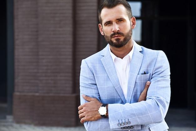El retrato del modelo atractivo atractivo del hombre de negocios de moda se vistió en el traje azul elegante que presentaba en fondo de la calle. metrosexual