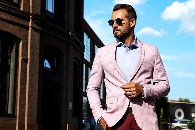 El retrato del modelo atractivo atractivo del hombre de negocios de la moda se vistió en el traje elegante que presentaba en fondo de la calle. metrosexual