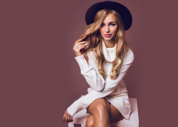 Retrato de modelo bastante rubia sentada en la mesa en suéter de punto cálido casual blanco y sombrero negro