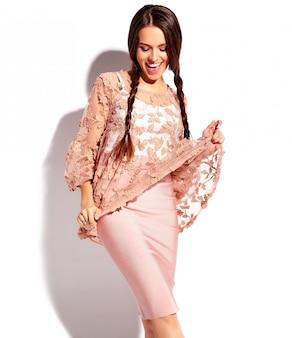 Retrato del modelo caucásico sonriente de la mujer morena hermosa con las coletas dobles en la ropa elegante del verano rosado brillante aislada en el fondo blanco.