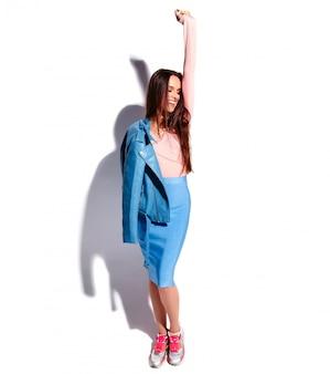 Retrato del modelo caucásico sonriente de la mujer morena hermosa en la ropa elegante del verano rosado y azul brillante aislada en el fondo blanco. longitud total